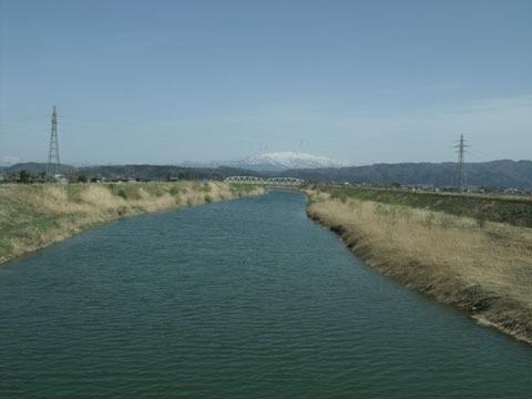 川の向こうに見えるのは越後山脈の山々